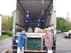 """Volunteers unload donations from a KANE trailer during last year's """"Stamp Out Hunger"""" food drive."""